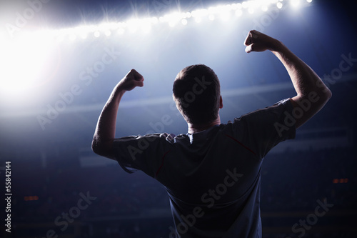 Fotografia  Soccer player with arms raised cheering, stadium at night time