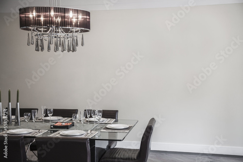 Dining room with modern furniture and chandelier. Poster