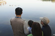 Family looking at ducks in a lake