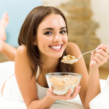 Young Woman Eating Cereal Musl...