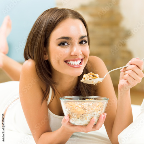 Canvas-taulu Young woman eating cereal muslin, flakes