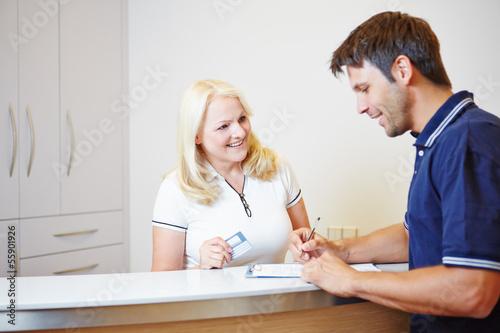 Leinwand Poster Patient redet mit Arzthelferin an Rezeption