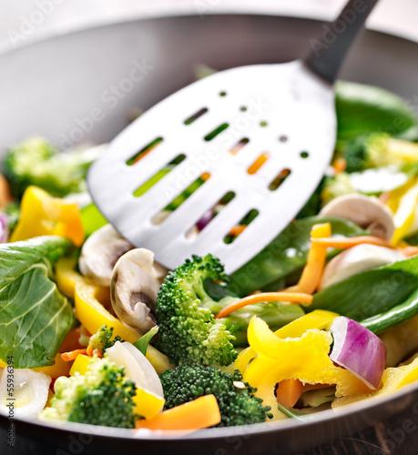 Photo  vegetarian wok stir fry with metal spatula.