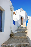 Narrow street with steps and white houses in Oia