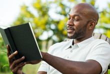 Handsome Black Man Reading Boo...