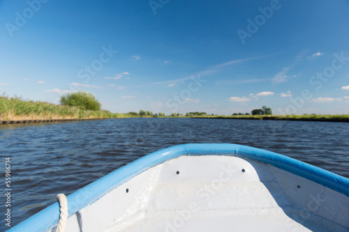 Foto  Blue boat on river