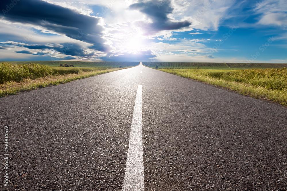 Fototapeta Driving on empty road towards the sun