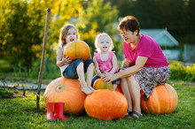 Two Little Sisters Sitting On A Huge Pumpkins