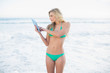 Concentrated blonde woman in green bikini using a tablet pc