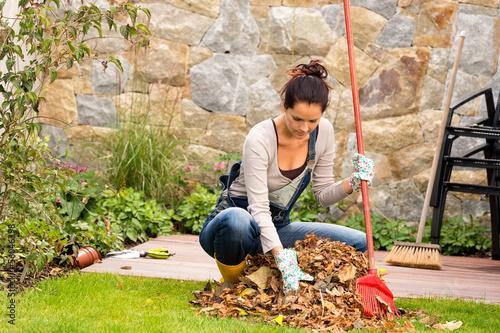 Fotografía Young woman raking leaves autumn pile veranda