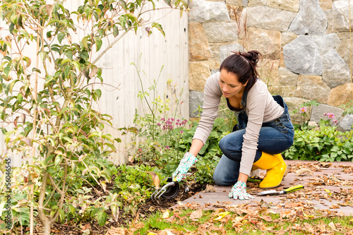 Canvas-taulu Young woman planting backyard flowerbed autumn