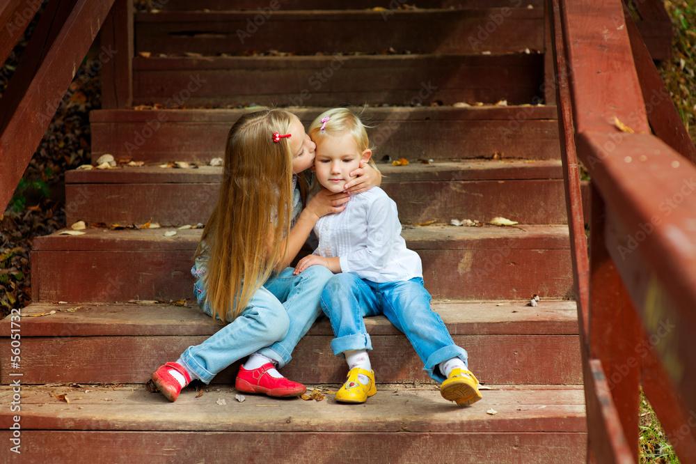 Zwei entzückende europäische Schwestern, die sich halten und küssen ...