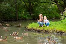 Two Cute European Sisters Feeding Ducks
