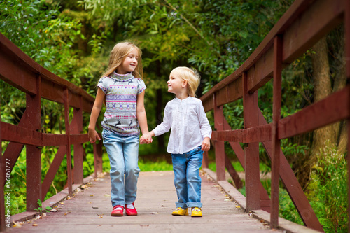 Photo  Two cute european blond sisters on scenic bridge together