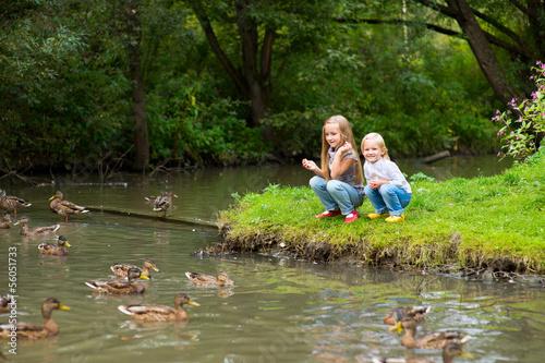 Photo  Two cute european sisters feeding ducks