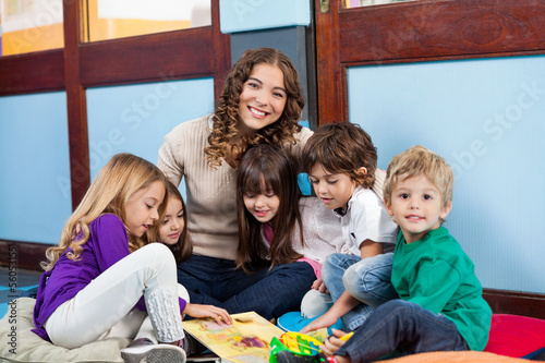 Valokuva  Teacher Sitting With Children On Floor