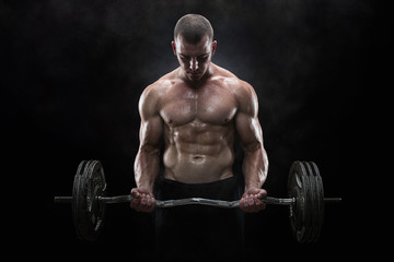 Fototapeta Young muscular man lifting weights over dark background