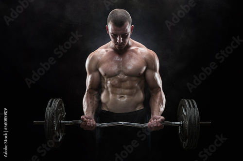 Fotografia  Young muscular man lifting weights over dark background