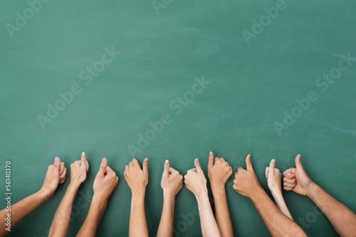 Foto  studenten zeigen daumen hoch an der tafel
