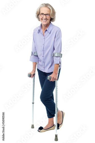 Bespectacled old woman walking with crutches Fototapeta