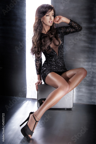 Attractive brunette woman sitting in elegant dress.