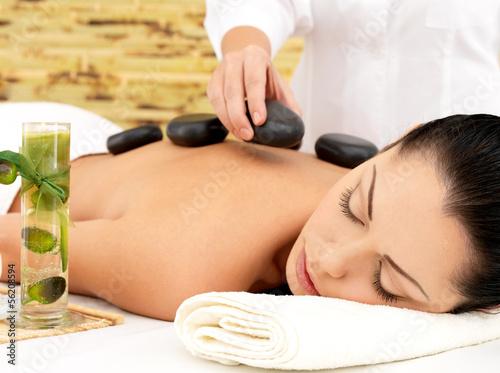Plissee mit Motiv - Woman having hot stone massage of back in spa salon