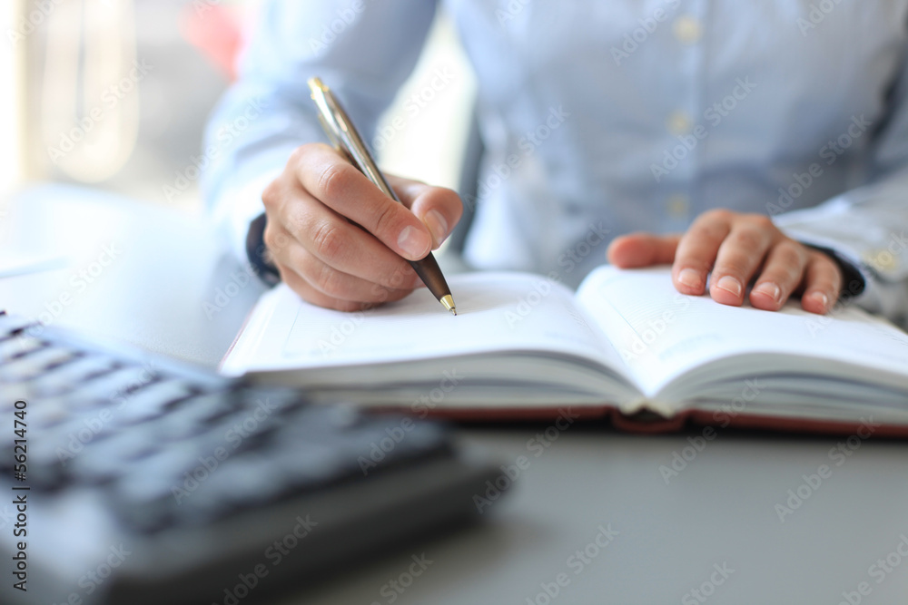 Photo  Businesswoman makes a note in notebook.
