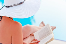 Girl In A Hat Reading A Book Near The Pool