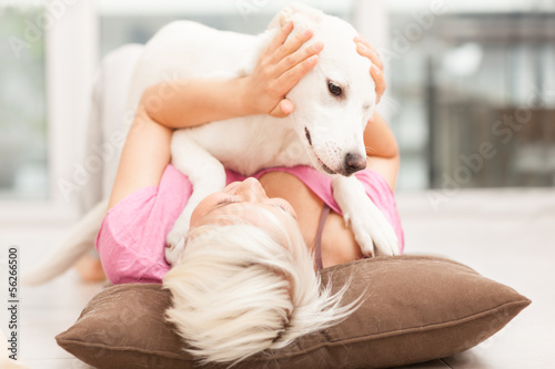 Fényképezés  Blonde woman is playing with her dog
