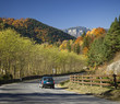Moving car on road in autumn mountain landscape