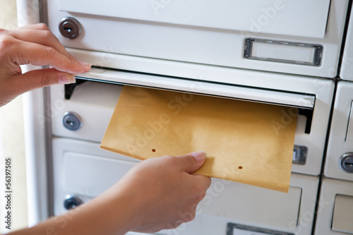 Fotomural Woman putting envelope in mailbox