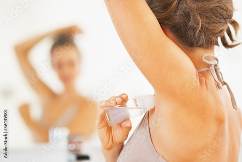 Closeup on woman applying roller deodorant on underarm Wallpaper Mural