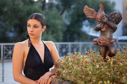 Valokuva  Young sexy woman with black dress posing outdoor
