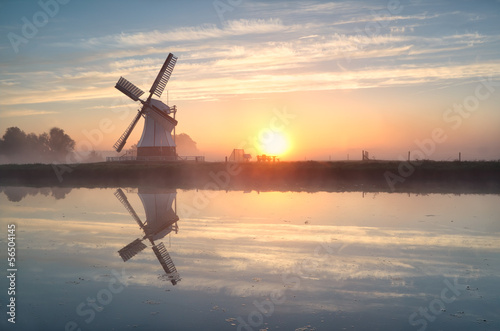 Dutch windmill reflected in river at sunrise Poster
