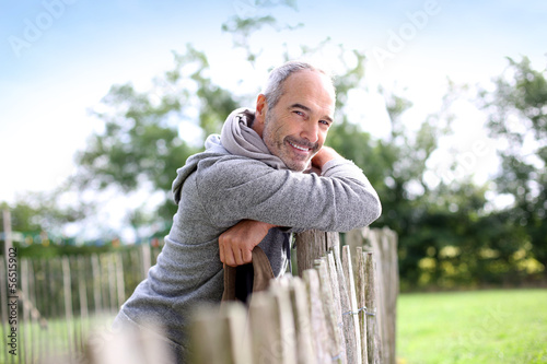 Mature man standing by fence in countryside