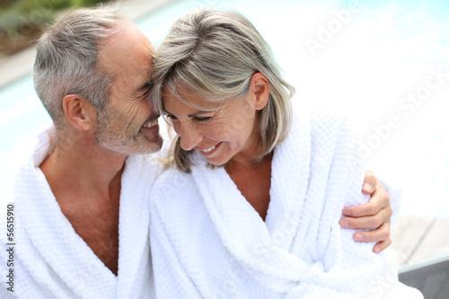 Fotografie, Obraz  Šťastný starší pár v županu od resortu bazénu