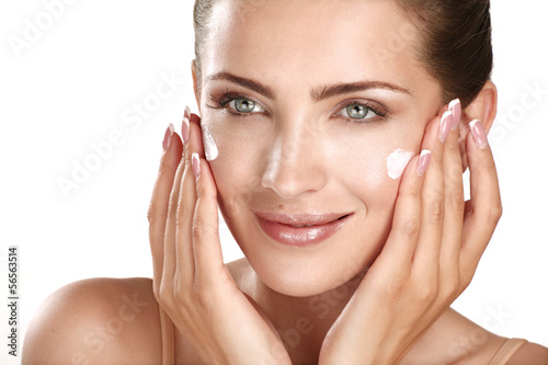 Fotografie, Obraz  beautiful model applying cosmetic cream treatmen on her face