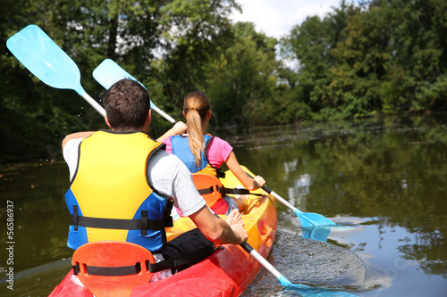 Leinwand Poster Couple riding canoe in river