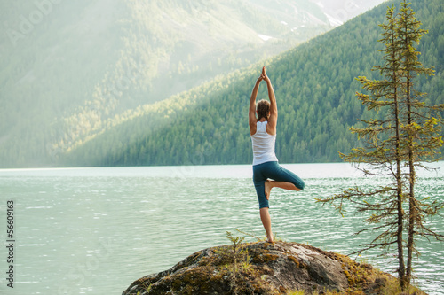 Valokuva Young woman is practicing yoga at mountain lake