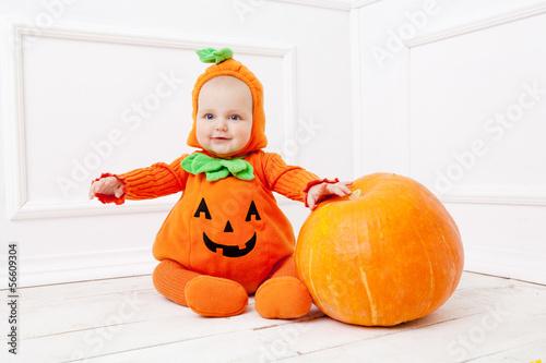 Fotografía Child in pumpkin suit on white background with pumpkin