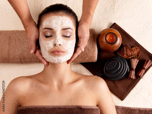 Spa massage for woman with facial mask on face Canvas Print