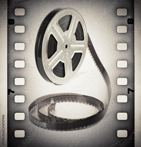 In de dag Retro Old motion picture film reel with film strip. Vintage background