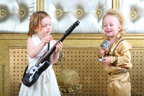 a little girl plays guitar and pop musician sings song buy this