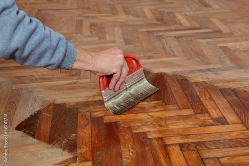 Fotografie, Obraz  Varnishing of oak parquet floor, workers hand, brush, renovation