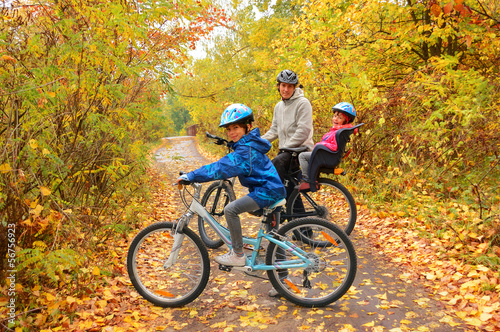 Photo Stands Cycling Happy family on bikes in autumn park, having fun