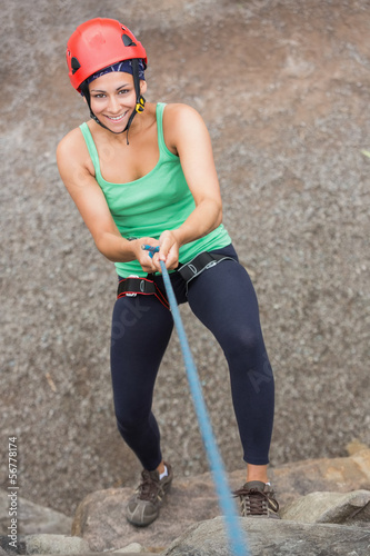 Smiling girl abseiling down rock face Wallpaper Mural