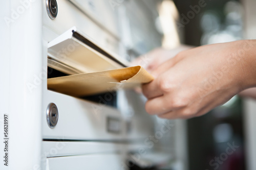 Fotografie, Obraz  Woman putting envelope in mailbox