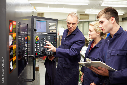 Fotografie, Obraz  Engineer Teaching Apprentices To Use Computerized Lathe
