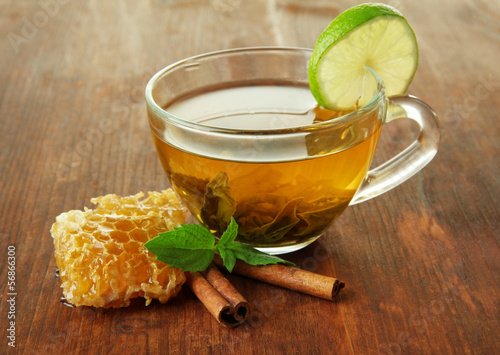Transparent cup of green tea with honey and cinnamon - 56866300