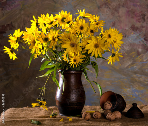 Bunch of bright yellow flowers (rudbeckia) in brown vase and wal